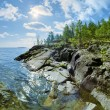 Sun and stony shore of Ladoga lake — Stock Photo #44547365