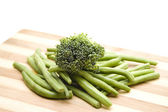 Green Broccoli with Green String beans on wooden plate — Stock Photo
