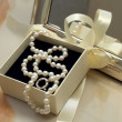 Pearl necklace in a gift box in front of a mirror — Stock Photo