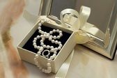 Pearl necklace in a gift box in front of a mirror — Stockfoto