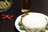 Cheese with green olives and red chili peppers — Stock Photo