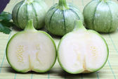 Round zucchini on a green bamboo tablecloth — Stock Photo