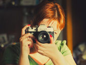 Close -up of the young woman having control over the antiquarian camera. — Stock Photo
