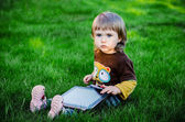 Boy sitting on grass and using computer — Stock Photo