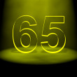 Number 65 illuminated with yellow light - Stock Photo