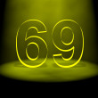 Number 69 illuminated with yellow light - Stock Photo