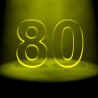 Number 80 illuminated with yellow light - Stock Photo