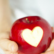 Hand with apple, which cut heart — Stock Photo #18385905