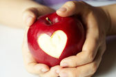 Hand with apple, which cut heart — Stockfoto