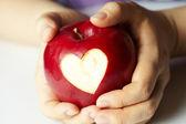 Main avec apple, pour coupe le coeur — Photo