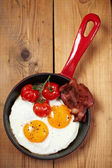 Fried eggs with bacon and tomatoes — Stock Photo
