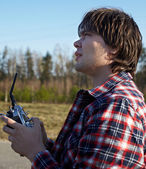 Young man controls RC plane in the sky — Stock Photo