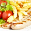 Grilles sausages with french fries and salad - Stock Photo