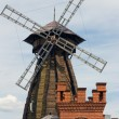 A windmill and a brick tower — Stock Photo