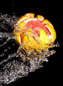 Carved grapefruit in a stream of water — Stock Photo