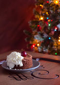 Chocolate dessert and Christmas tree — Stock Photo