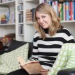 Young, attractive woman sits on the couch and reads a book — Stock Photo
