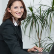 Young attractive businesswoman uses her laptop — Stock Photo