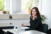 Businesswoman sits at a table — Stock Photo