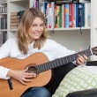Pretty young woman plays guitar — Stock Photo