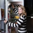 Woman stands in front of the fridge — Stock Photo