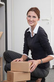 Businesswoman sorts parcels — Stock Photo