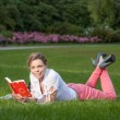 Pretty young woman reads a book — Stock Photo