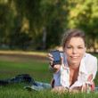 Young, attractive woman shows her smartphone — Stock Photo