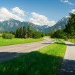 Street heading to the alps — Stock Photo