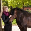 Girl strokes pony — Stock Photo