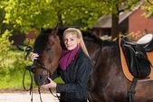 Girl bridles her pony — Stock Photo