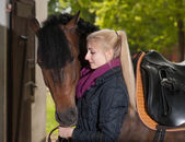 Girl looks to her horse — Stock Photo