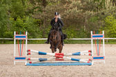 Girl is show jumping with her horse — Photo