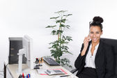 Young business woman phones at the desk — Stock Photo
