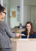 Clerk is handing over a document to a customer — Stock Photo