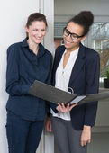 Two women are looking at a file — Stock Photo