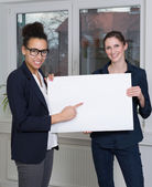 Two women are showing a whiteboard — Stock Photo