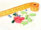 Diet pills and a tape measure — Stock Photo