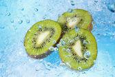 Water splashing on kiwi slices-top view — Stock Photo
