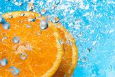 Orange splash in water, top view — Stock Photo