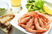 Dish of fresh boiled prawns with lettuce, some bread and beer — Stock Photo