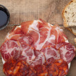 Dish of sliced smoked ham and sausage - top view — Stock Photo