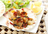 Fried scallops in the shell with salad — Stock Photo