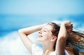 Young beautiful woman with streaming hair in front of the ocean — ストック写真