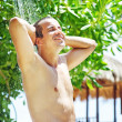 Attractive young man having a shower in a tropical garden with palm trees while on holiday — Stock Photo