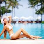 Young beautiful woman sitting near swimming pool — Stock Photo