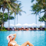 Young beautiful woman sitting near swimming pool — Stock Photo #19926015