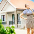 Happy woman in front of new home - Stock Photo