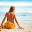 Beautiful woman sitting from the back on beach, bali — Stock Photo #19926343