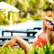Young beautiful woman outdoors sitting on the chair near swimming-pool — Stock Photo